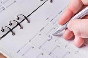 caneta prata, escrevendo no calendário de agenda de negócios abertos foto