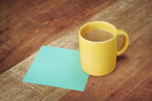 nota em branco e xícara de café na mesa de madeira foto