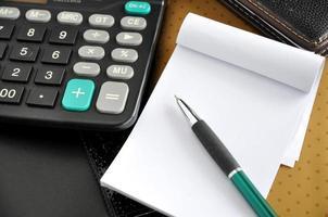 caneta no papel em branco com calculadora foto