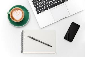 laptop, celular de tela em branco, xícara de café, bloco de notas e caneta foto