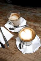 café e talheres com espuma em forma de coração