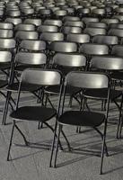 linhas vazias de cadeiras de plástico pretas foto