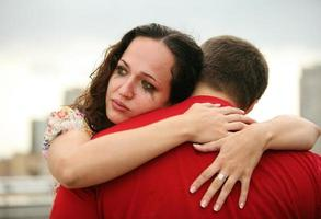close-up da mulher, abraçando o homem e chorando com maquiagem em execução foto