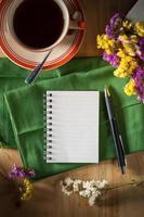 bloco de notas com caneta na mesa de madeira foto