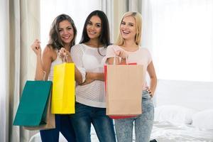 alegres três meninas com muitos sacos de compras foto
