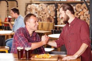 rapazes bonitos estão reunidos em cervejaria foto