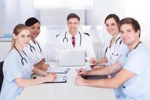 médicos em reunião com a área de transferência e laptop foto