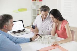 agente imobiliário mostrando o projeto de construção para um casal foto