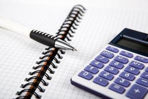 caneta em um notebook em uma célula e calculadora foto