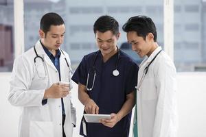 equipe de médicos do sexo masculino usando um tablet digital foto