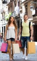 jovem par amoroso com sacos de compras na cidade foto