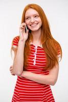 feliz mulher jovem com longos cabelos vermelhos falando no celular foto