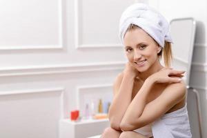agradável mulher sentada no banheiro foto