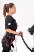 jovem cabe exercício de mulher na máquina de estimulação eletro muscular foto