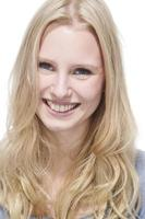 jovem mulher loira sorrindo contra retrato de fundo branco foto
