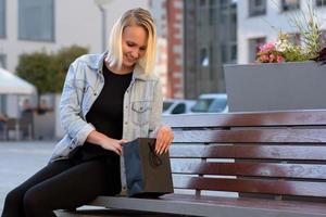 jovem mulher verificando suas compras ou presente foto