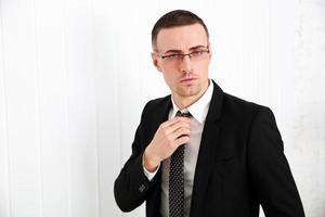 empresário de óculos, ajustando a gravata