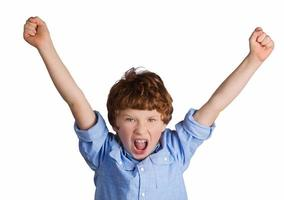 garoto bonito comemorando a vitória. isolado no fundo branco foto