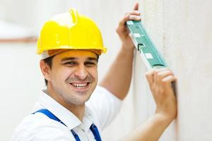 trabalhador profissional com nível de bolha na parede foto