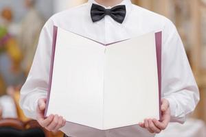 vista do peito de um garçom no restaurante segurando um menu em branco foto