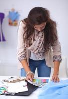 designer de moda jovem moderna trabalhando no estúdio. foto