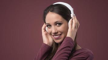 mulher sorridente com fones de ouvido foto