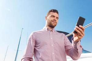 homem agradável, segurando o telefone móvel foto