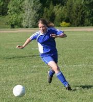 jogador de futebol jovem adolescente perseguindo a bola foto