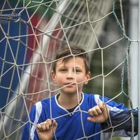 pequeno jogador de futebol por trás do gol de futebol. foto