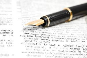 caneta-tinteiro e livro de dicionário