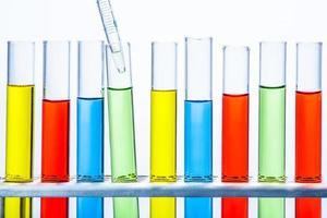 pipeta de laboratório com gota de líquido sobre tubos de laboratório de teste foto