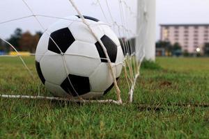 bola de futebol no gol líquido e fundo da cidade foto