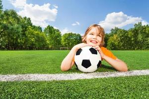 menino sonhador detém futebol, olhando e deitado