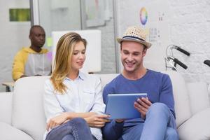 colegas casuais usando tablet digital no sofá no escritório foto