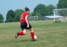menina no campo de futebol chutando bola foto