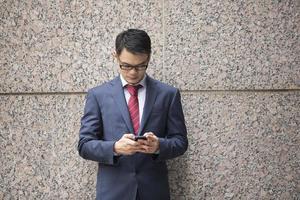 homem de negócios chinês usando um smartphone. foto