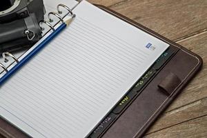 diário com câmera retro em uma mesa de madeira foto