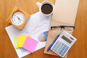 caderno e gráfico na mesa de madeira com café foto