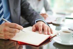 mão com caneta e bloco de notas foto