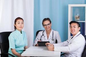 médicos felizes conversando no escritório foto