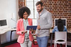 colegas casuais usando tablet digital no escritório foto