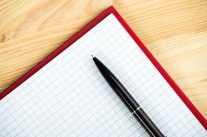 caderno em branco com caneta e lápis na mesa de madeira