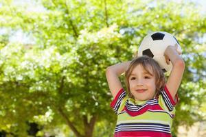 menino feliz, segurando o futebol foto