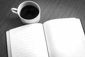 caderno vazio e café na mesa de madeira foto