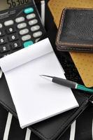 caneta e papel com calculadora no fundo foto