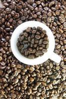 xícara cheia de grãos de café torrados