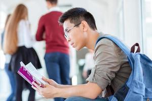 livro de leitura do estudante do sexo masculino no salão da universidade foto