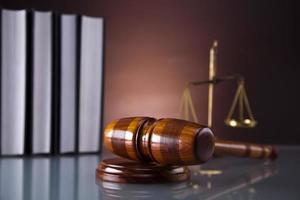 balança dourada da justiça, martelo e livros foto
