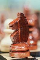 cavalo de xadrez marrom de madeira velho em pé no tabuleiro de xadrez foto