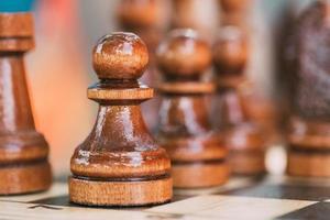 peão de xadrez velho em pé no tabuleiro de xadrez de madeira foto